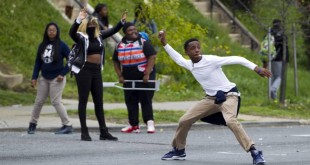 Demonstrators throw rocks at the police after the funeral of Freddie Gray on Monday, April 27, 2015, at New Shiloh Baptist Church in Baltimore. Gray died from spinal injuries about a week after he was arrested and transported in a Baltimore Police Department van. (AP Photo/Jose Luis Magana)